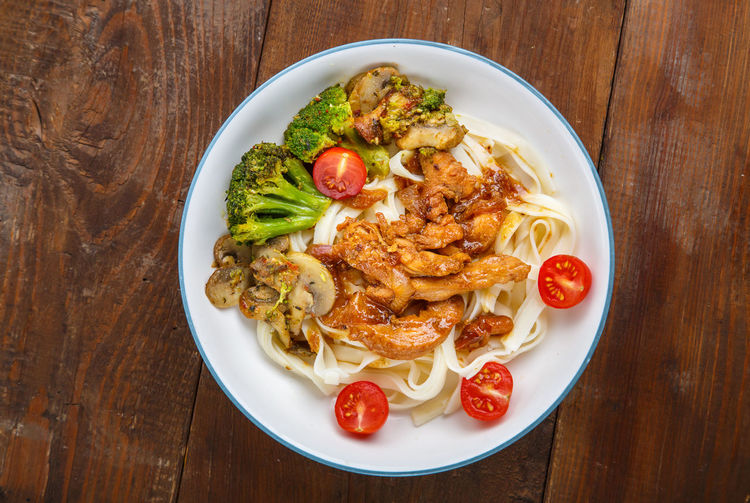 Udon with meat and vegetables in yakiniku sauce in a gray plate on a wooden table. horizontal photo