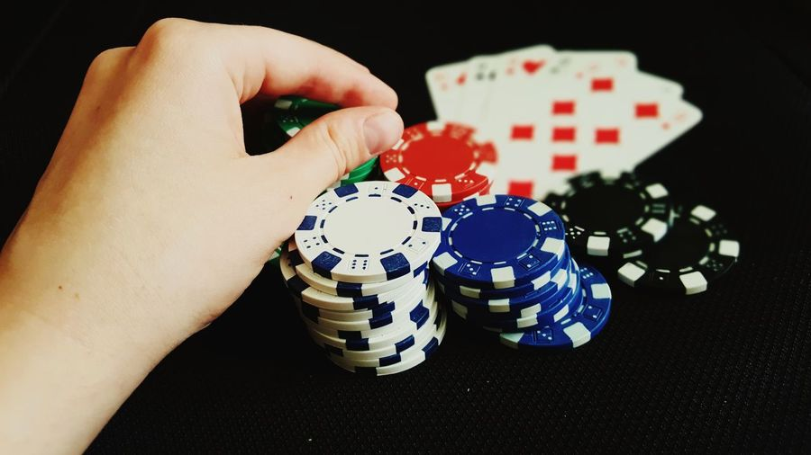 EyeEm Selects Gambling Human Body Part Leisure Games Human Hand One Person Playing Gambling Chip Poker - Card Game Indoors  Luck People Strategy Leisure Activity Woman Casino Poker Night Cards