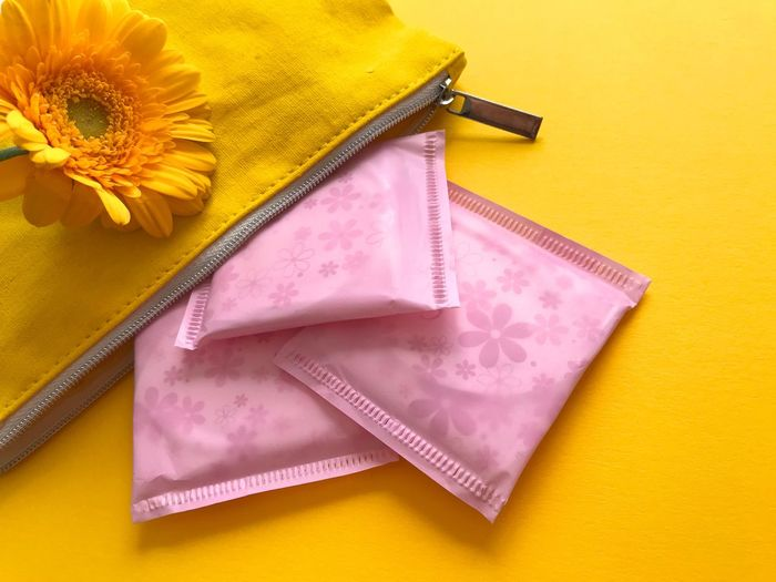 Women's Health : Menstruation. Sanitary pads and a makeup bag with a fresh yellow flower on a yellow background with copy space Copy Space Sanitary Pads Sanitary Napkins Healthcare And Medicine Well-being Women's Health EyeEm Selects Menstruation Menstrual Cycle Mense Feminine Hygiene Yellow Flower Still Life Indoors  No People High Angle View Studio Shot Pink Color Close-up Colored Background Directly Above Yellow Background Vibrant Color