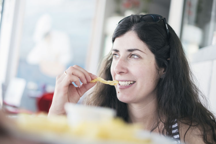 Smiling mid adult woman eating potato chip at restaurant