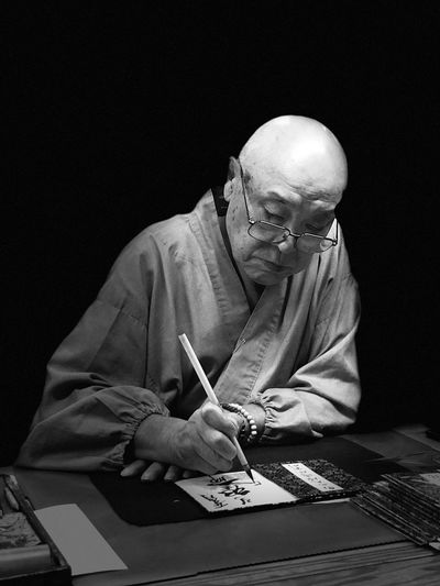 Senior man writing at table against black background