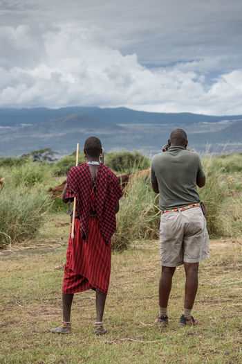Two african men, one in traditional dress, look out over a field. African Back View Cloud-sky Field Grass Masai Men Traditional Traditional Clothing