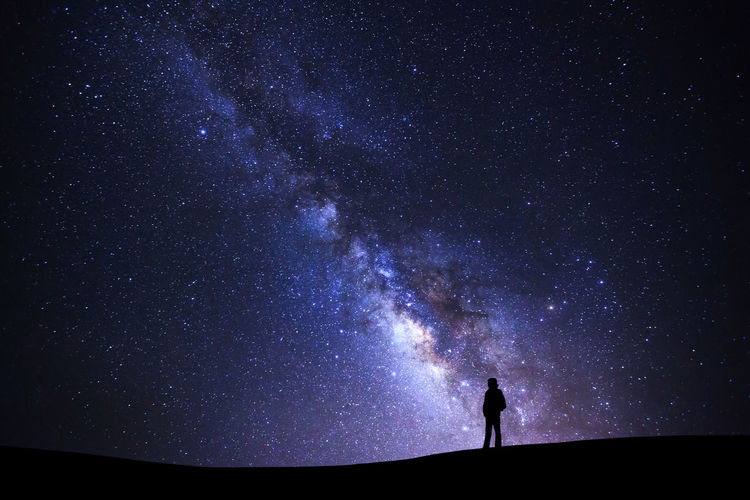 Low angle view of silhouette person standing on field against star field