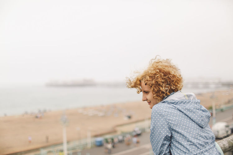 Woman At Brighton Pier Looking At Beach Against Clear Sky
