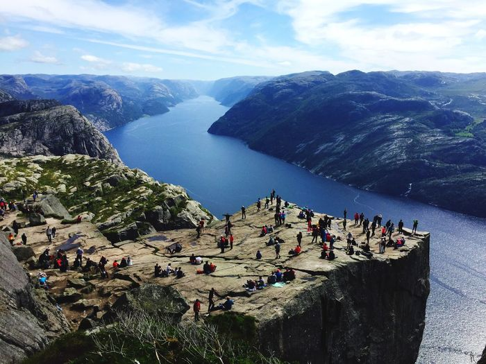 High angle view of people on cliff by lake against sky