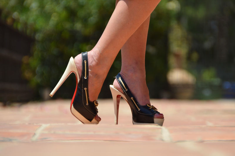 Low section of woman in high heels while walking on street