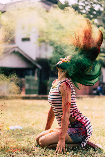 Woman splashing powder paint with hair while sitting on field
