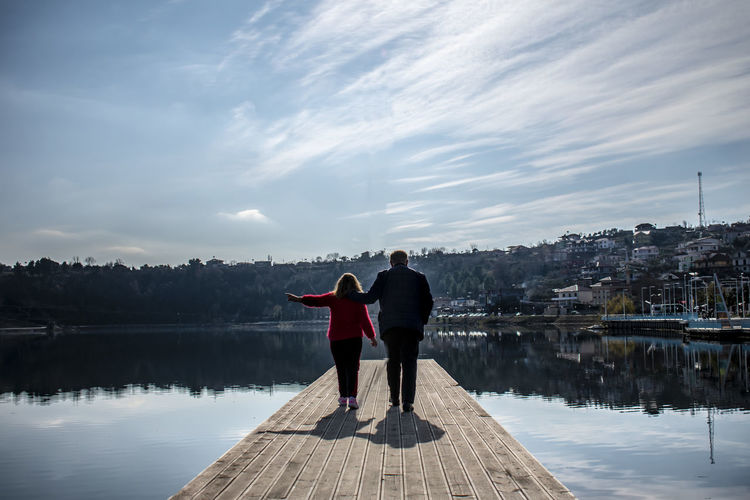 Rear view of women standing on pier over lake against sky