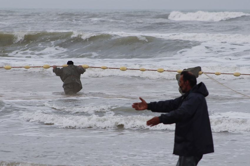 Real People Water Sea Rear View Leisure Activity Standing Nature Wave Lifestyles Men Outdoors Day Holding Beauty In Nature Horizon Over Water Two People Women Motion Sky Warm Clothing