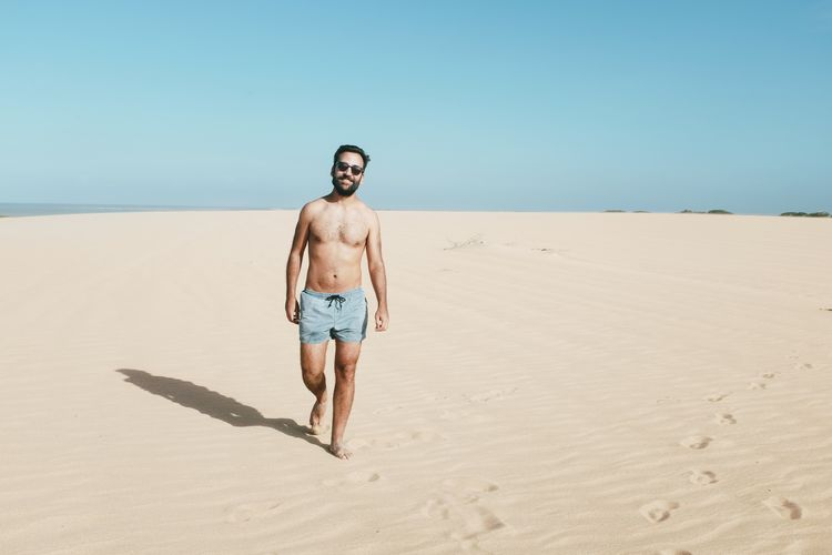 Full Length Of Shirtless Man Walking On Sand At Beach