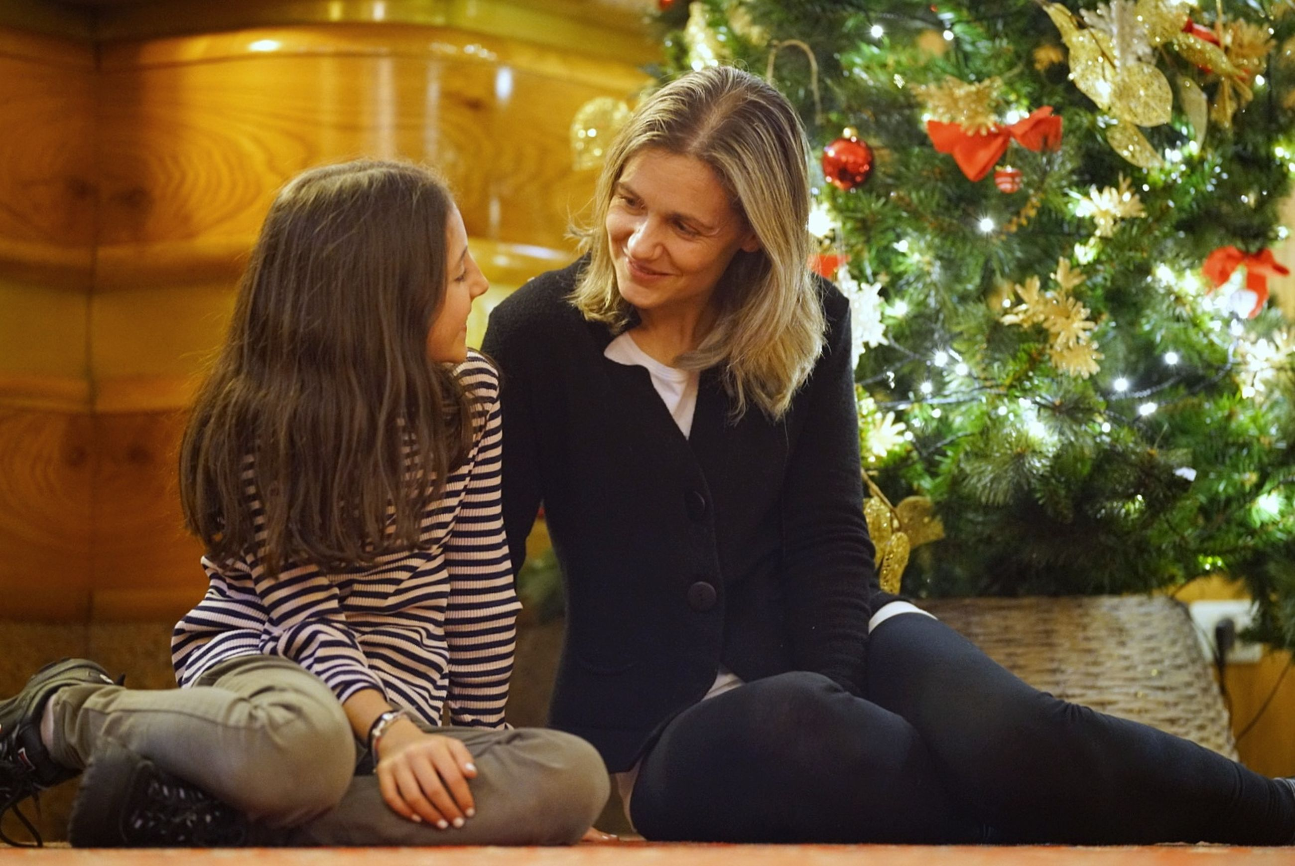 two people, women, bonding, togetherness, tree, sitting, christmas tree, emotion, lifestyles, real people, christmas, females, three quarter length, adult, happiness, love, positive emotion, smiling, holiday, hair, hairstyle, daughter