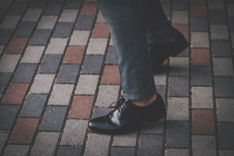 Low section of businessman wearing shoes while standing on footpath