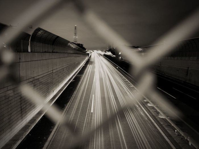 Blurred motion of railroad tracks by chainlink fence