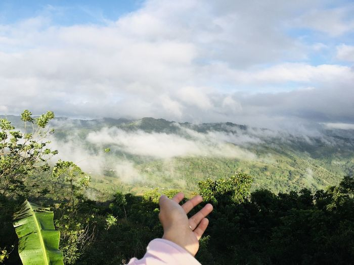 Cropped hand of woman against mountains