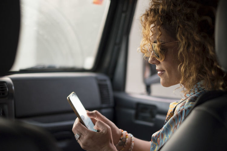 Side view of woman using smart phone in car