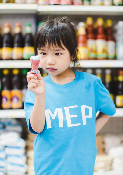 One Person Food And Drink Childhood Child Front View Store Holding Standing Waist Up Food Retail  Casual Clothing Focus On Foreground Girls Portrait Innocence Indoors  Supermarket Choice Bottle Bangs Hairstyle