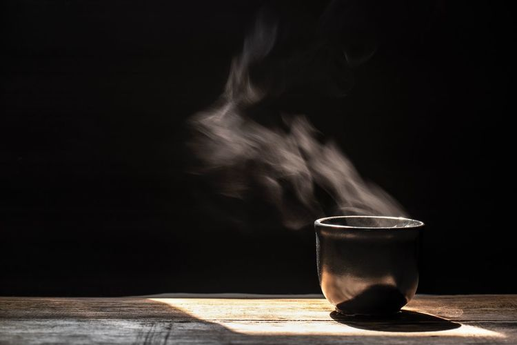 Hot tea cup with smoke on black background Hot Drink Dark Black Smoke Drink Refreshment Food And Drink Smoke - Physical Structure Table Indoors  Household Equipment Still Life Cup Mug Close-up Freshness No People Glass Copy Space Drinking Glass Hot Drink Heat - Temperature Coffee - Drink Coffee