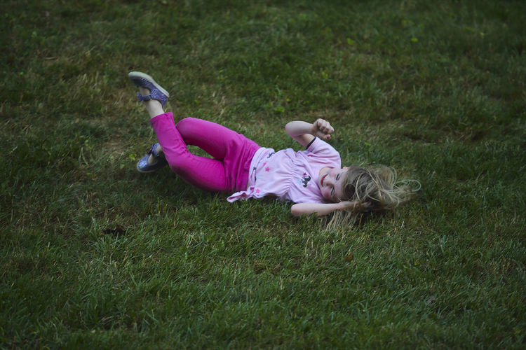 A five-year-old girl rolls down a hill near dusk during her summer vacation. Childhood Children Only Day Dusk Elementary Age Field Full Length Girls Grass Happiness Joy Joyful Leisure Activity Lifestyles Lying Down Music Festival Nature No School One Person Outdoors Real People Summer SUMMER BREAK Summer Vacation Summertime Sommergefühle