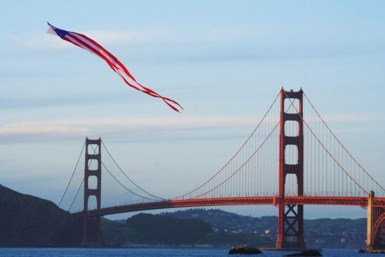 American flag kite flying against golden gate bridge over san francisco bay