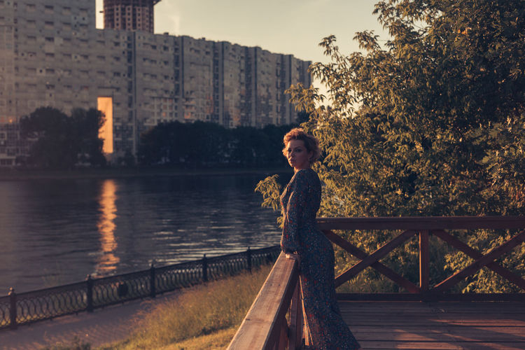 Portrait of woman standing by railing against lake