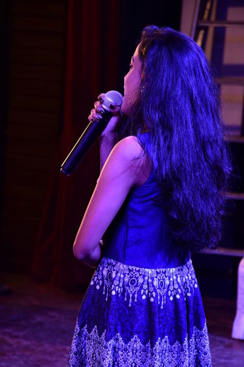 Side view of woman singing on stage