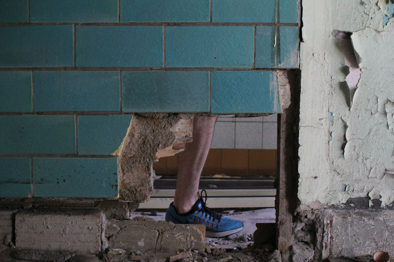 Low Section Of Man Standing By Damaged Wall