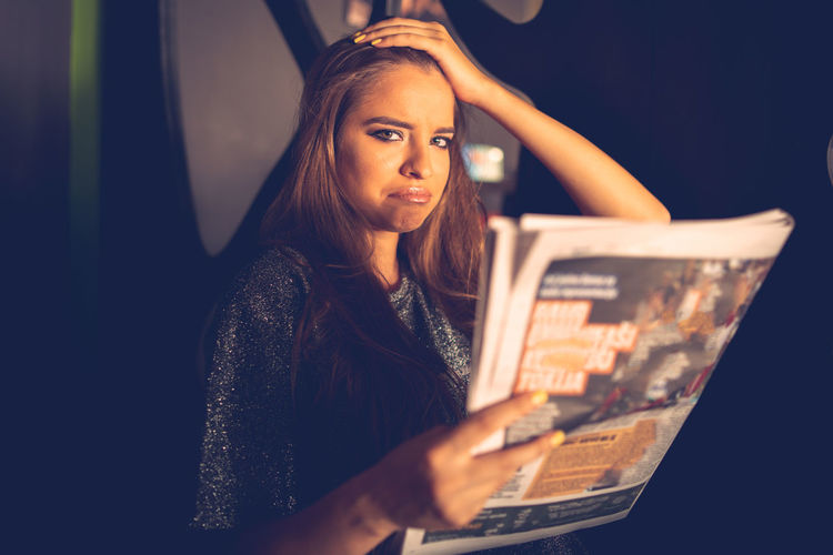 Portrait of sad young woman with magazine at home