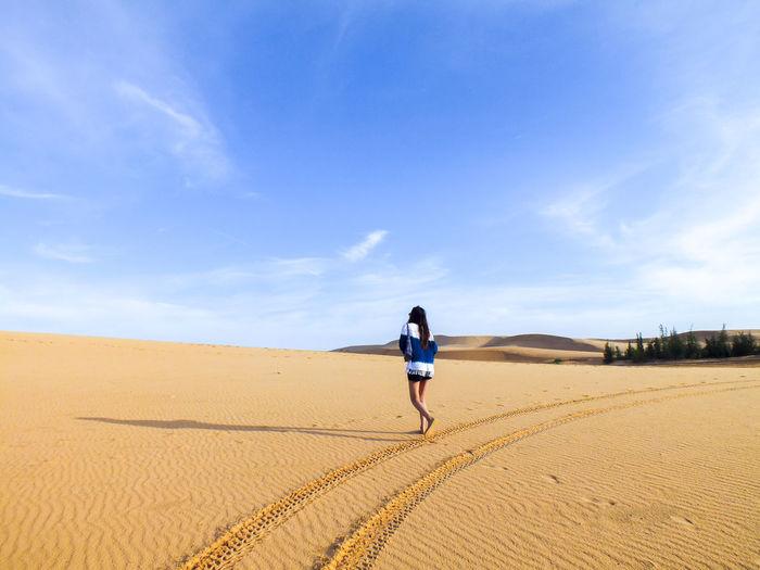 Rear view of women walking in desert against sky