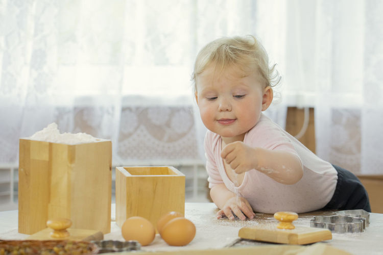 Portrait of cute boy preparing food on table at home