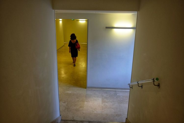 Rear view of woman walking in underground walkway