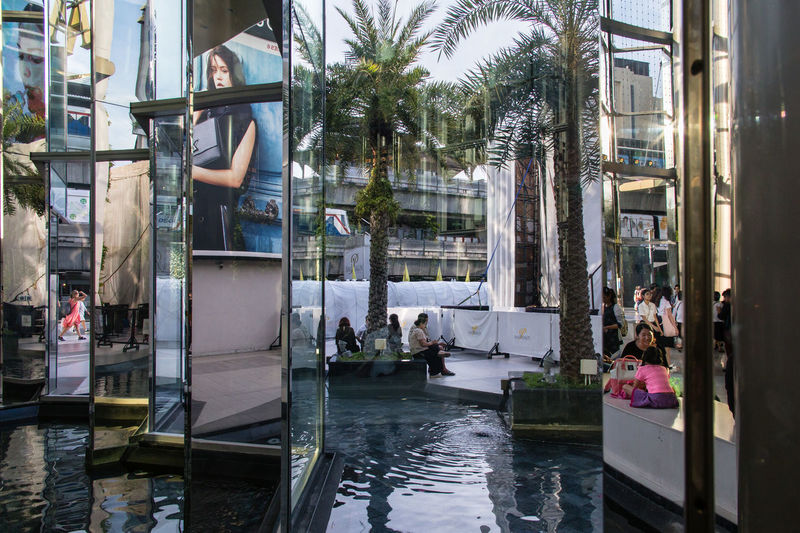 Siam Paragon shopping center in Bangkok, Thailand Architecture Building Exterior Built Structure City Large Group Of People Lifestyles Mirror Reflection Mirrors Multilayer Nature Outdoors Palm Tree Real People Reflection Reflections Shopping Center Shopping Centre Shopping Mall Siam Siam Paragon Street Photo Street Photography Streetphotography The Street Photographer - 2017 EyeEm Awards Water