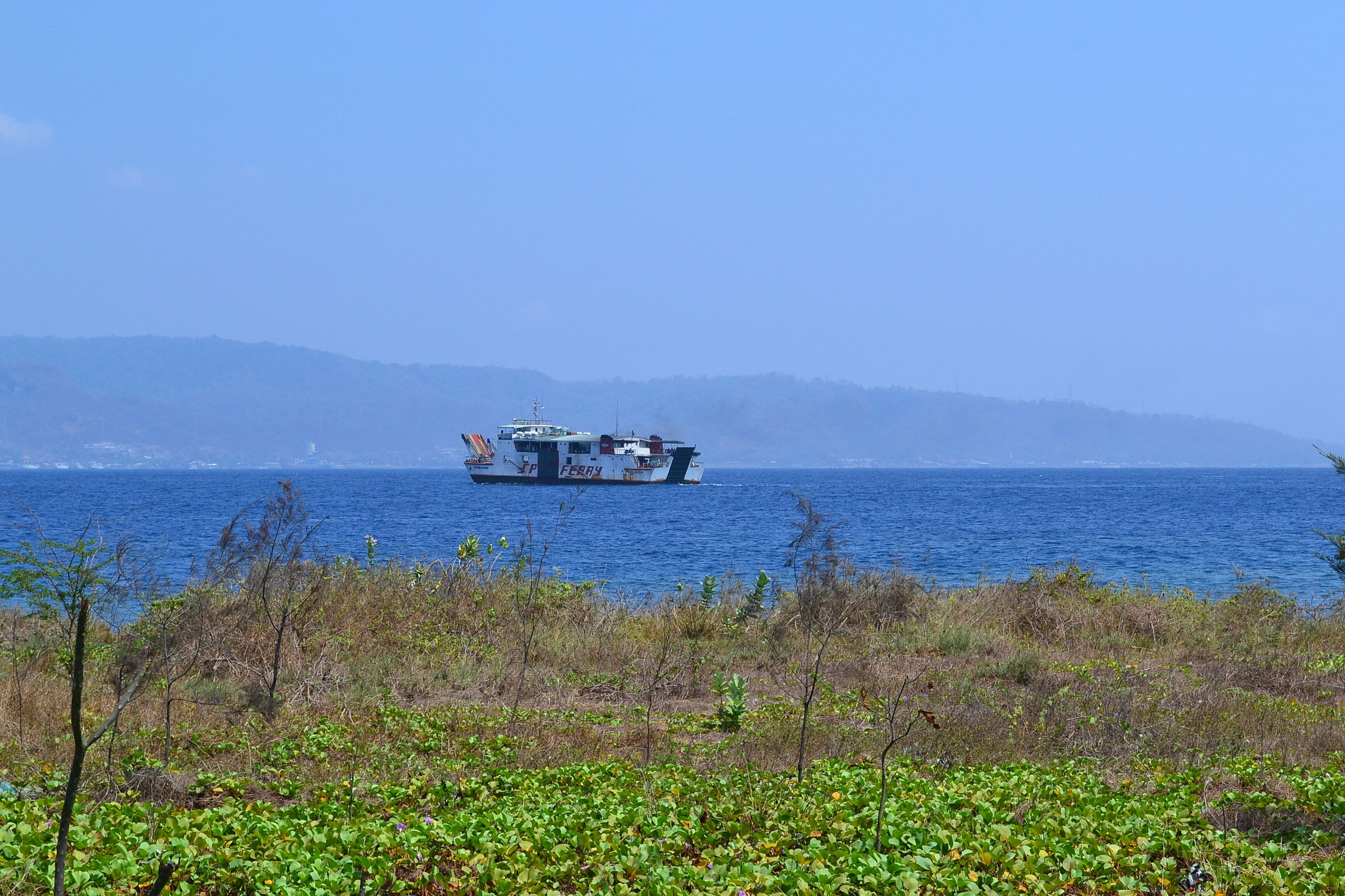water, clear sky, nautical vessel, transportation, sea, copy space, mode of transport, tranquil scene, beauty in nature, tranquility, scenics, blue, boat, nature, mountain, plant, horizon over water, growth, sky, grass