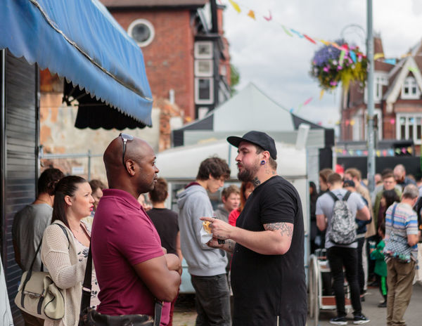 Two people discussing something at a public street festival in Kings Heath in Birmingham Black Man Bald Pointing Black Cap T Shirt Crowd Blured Background Streetphotography Reportage Street Featival Tatoo Neck Tattoo Heavy Tatooes Shallow Depth Of Field Editorial  Horizontal Public Event No Filter Unprocessed Full Frame Unshaven Eye Level Blurred Background