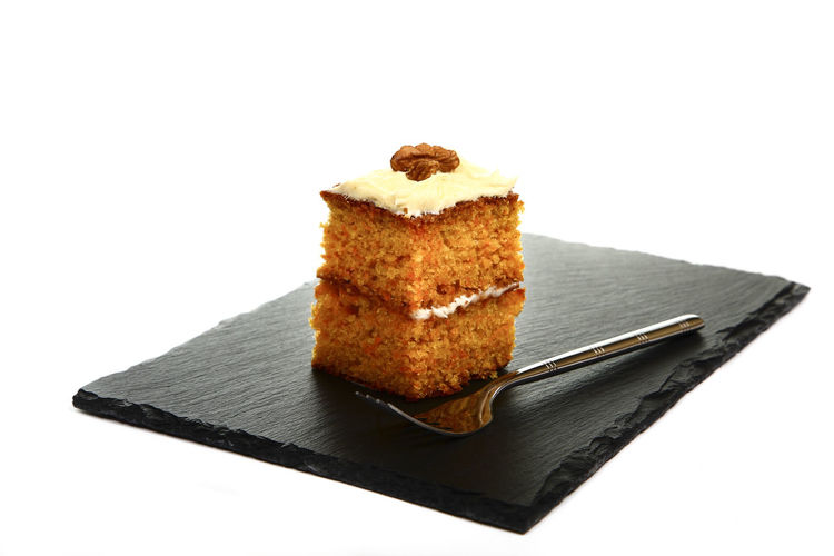 Slice of delicious homemade carrot cake served on a slate platter isolated on a white background Cakes Desert Fork Home Cooked Icing Baking Buttercream Cake Calories Carrot Cake Confectionery Cream Delicious Food Gourmet Home Made Cake Indulgence Piece Slate Slate Platter Sweet Tasty Treat Walnut