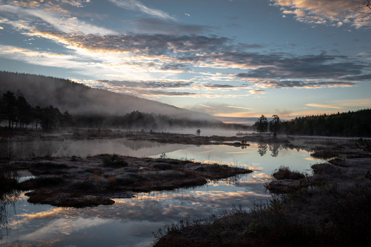 Picturesque natural landscape panorama in norway with mist rising above water and cloudscape