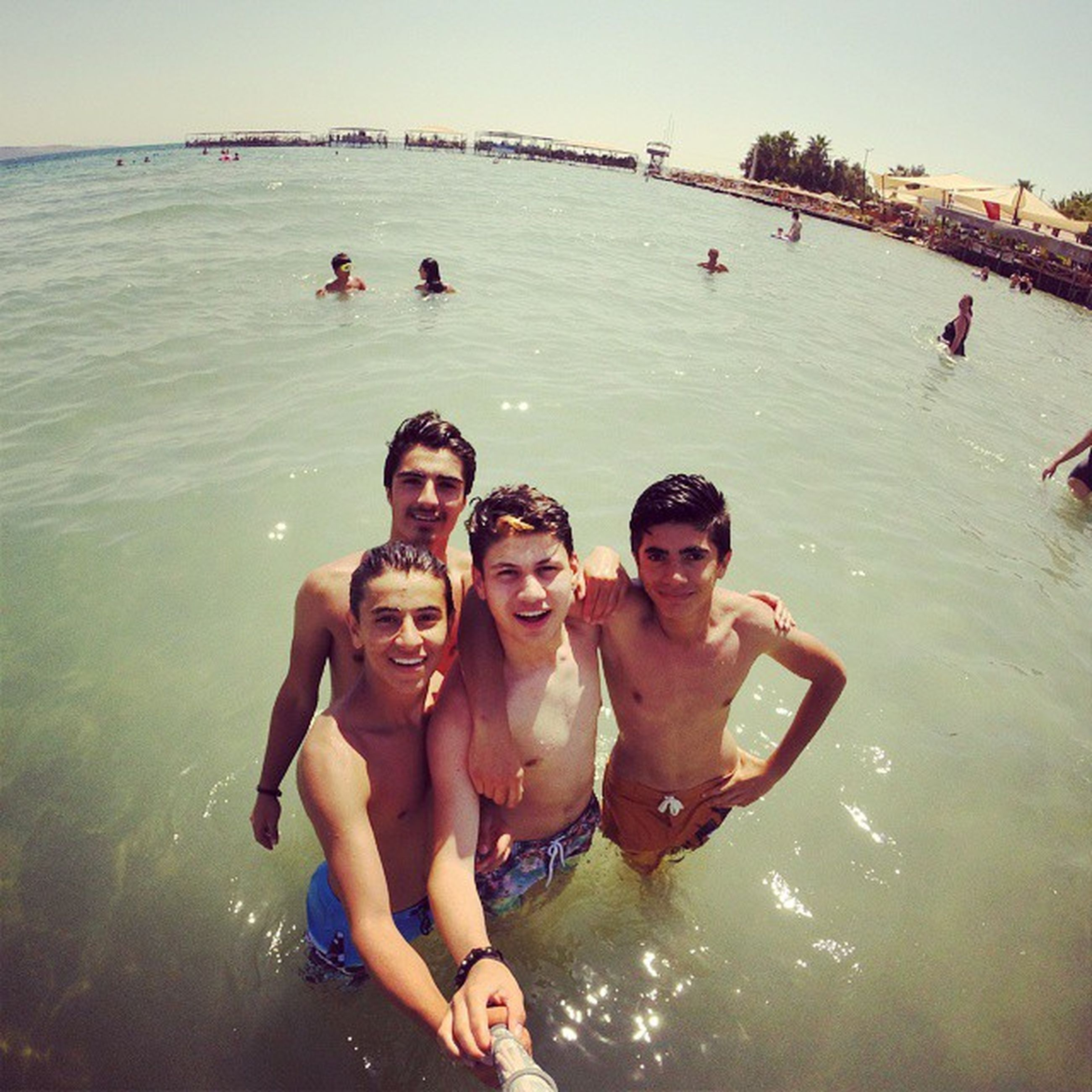 water, lifestyles, leisure activity, togetherness, vacations, sea, enjoyment, bonding, person, happiness, beach, love, shirtless, fun, friendship, high angle view, boys, family