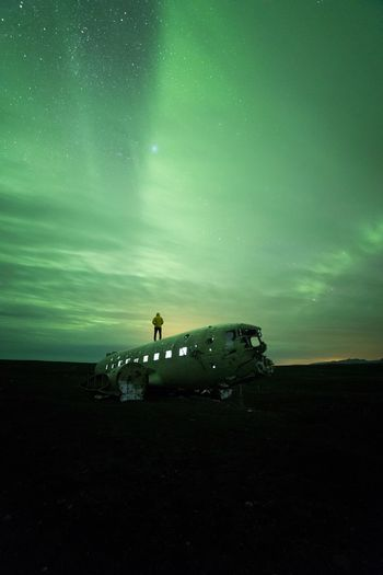 Man standing on dc-3 airplane against aurora borealis at night