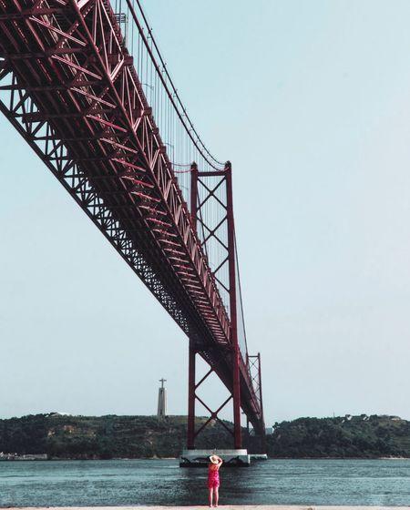 Rear view of woman standing below suspension bridge over against sky