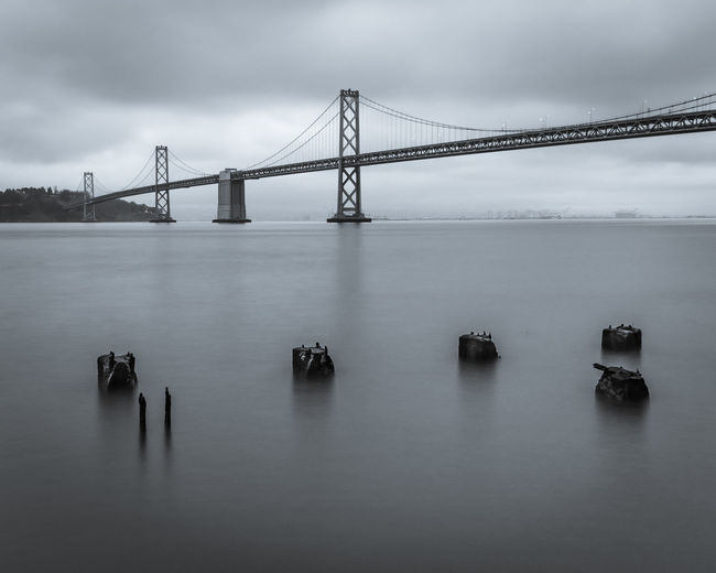 Low angle view of oakland bay bridge over sea against sky