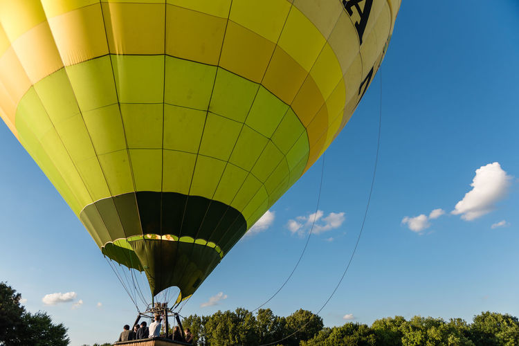 Low angle view of hot air balloon flying against blue sky