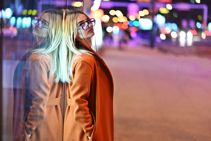 Midsection of woman standing by illuminated street at night