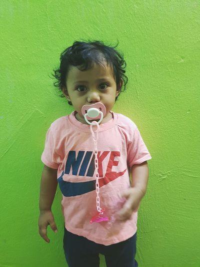 Cute girl standing against green wall