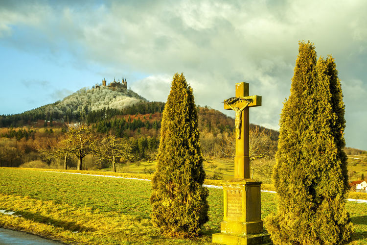 Religious cross on field against sky