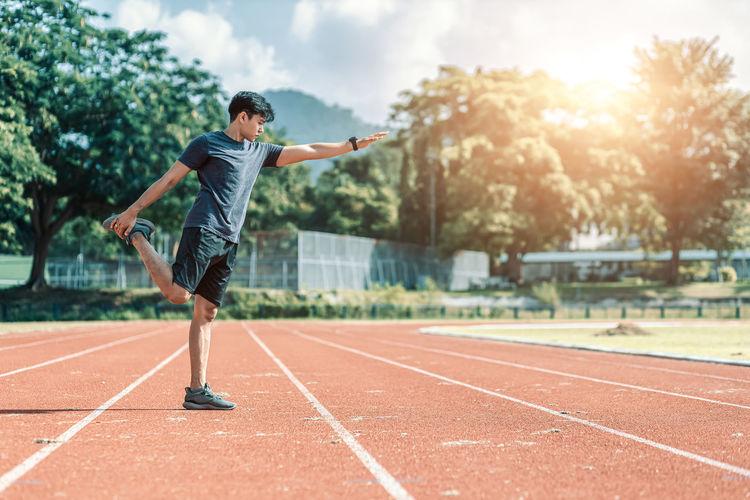 Full length of man exercising on track