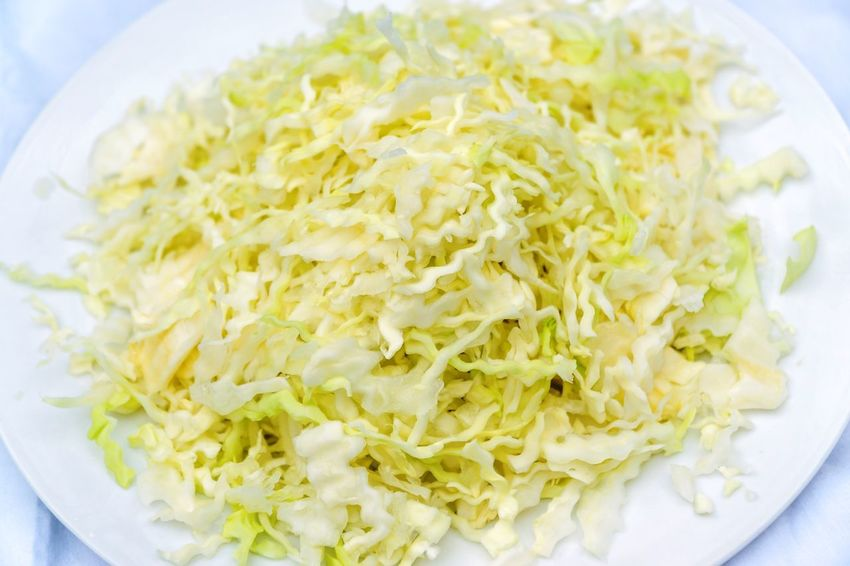 Shredded white cabage on a display plate Daytime Photography Food Raw White Cabage Shredded Cabage Table Vegetables White Cabage White Plate