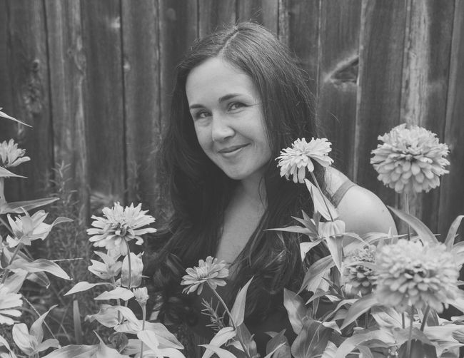 Portrait of smiling young woman by flowering plants