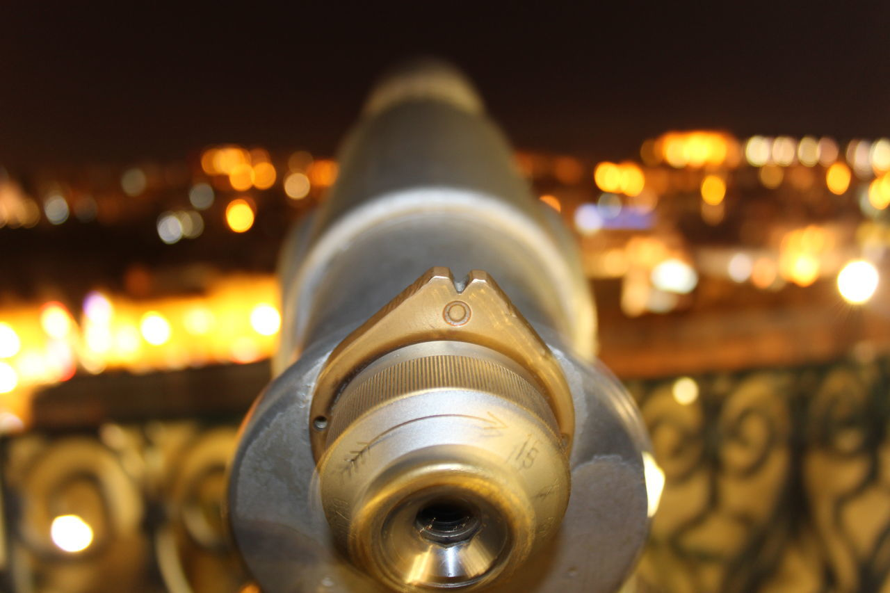 Close-up Of Coin-operated Binoculars In Illuminated City At Night