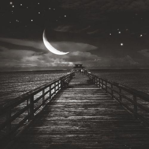 Pier on sea at night