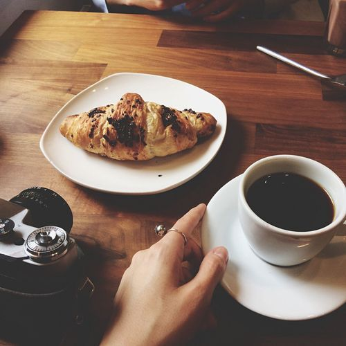 Cropped Hand Of Woman With Black Coffee At Table