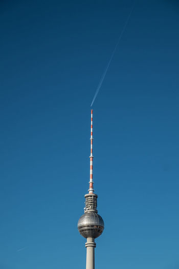 Low angle view of fernsehturm tower against clear blue sky